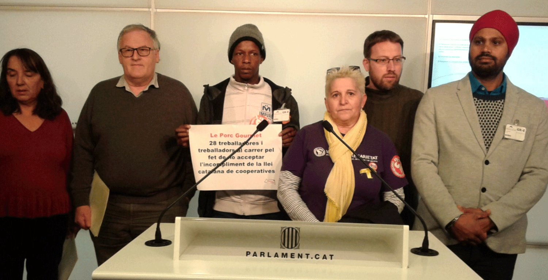 Montse Castañé, en la compareixença al Parlament, junt amb acomiadats i diputats que els donen suport foto: COS
